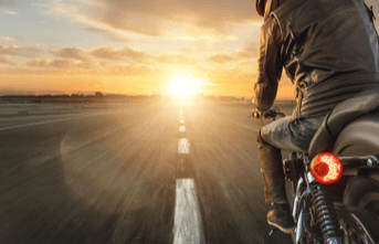 man riding motorcycle into sunset