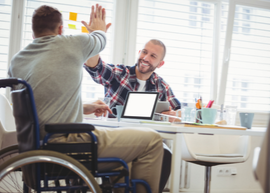 man in a wheel chair giving another man a high five